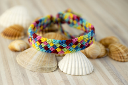 One simple handmade homemade natural woven bracelets of friendship on white wooden table with sea shells