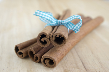 Fresh raw cinnamon sticks on wooden table tied with light blue checkered bow, low depth of field Reklamní fotografie