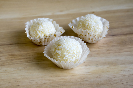Raw coconut balls in paper cupcakes Stock Photo