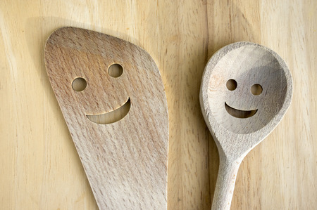 table top: Two funny smiling wooden equipment on wooden kitchen table, wooden spoon and wooden spatula Stock Photo