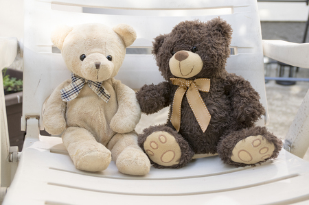 Two cute bears sitting on white sitting and talking, eye contact, beige teddy bear and dark brown bear, both with ribbon Stock Photo