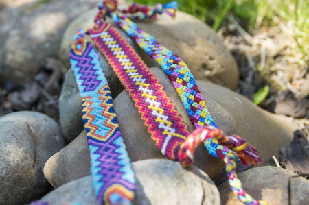Natural bracelets of friendship in a row, colorful woven friendship bracelets, background, rainbow colors, checkered pattern Stock Photo