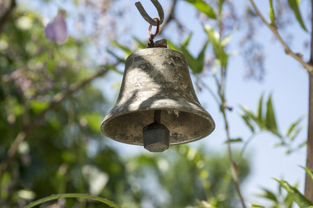 Small metallic oriental bell hanging in the garden, sunny day, greenery around