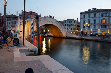 ITALY, CHIOGGIA - June 15, 2017 Early evening in Chioggia streets, romantic scene with canal, boats, old historic buildings and reflections, calm water and old bridge