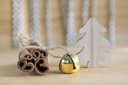Fresh raw cinnamon sticks on wooden table tied with red bow, jingle bell, reflections on background, Christmas tree and Christmas chains