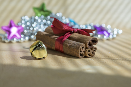 Fresh raw cinnamon sticks on wooden table tied with red bow, jingle bell, reflections on background, sunlight and shadows Stock Photo