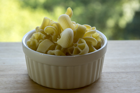 tortellini: Various mix of pasta in white baking bowl on wooden table, dry ingredients