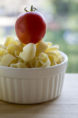Various mix of pasta in white baking bowl on wooden table and ripened red tomato on the top of pile Stock Photo