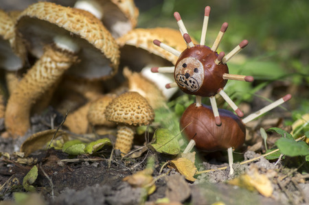 Two funny chestnut animal on tree stump, green background, traditional autumn handcraft, lion Stock Photo