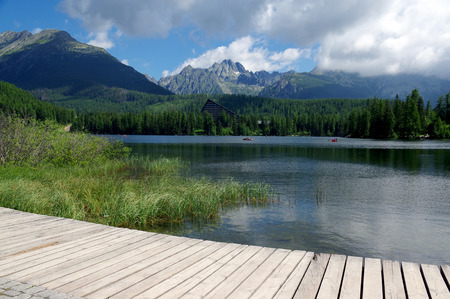 early summer: Strbske pleso, High Tatras mountains, Slovakia, early summer morning, lake reflections, wooden pier