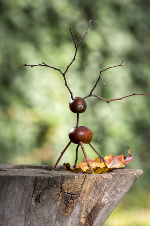 Chestnut animal on wooden stump, deer made of chestnut, acorn and twigs, green background