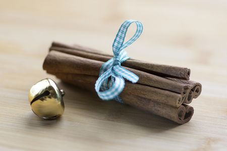Group of cinnamon tied with checkered light blue bow, golden jingle bell Stock Photo