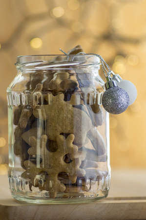 Christmas gingerbreads in glas jar with silver Christmas decorative balls with Christmas lights background Stock Photo