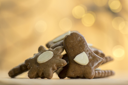 Brown moravian dark gingerbreads with sliced almonds, christmas cookies, Christmas lights reflections on background, bell and snowflake star shapes