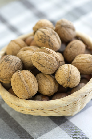 Walnuts in hard shells, pile on checkered tablecloth in creel Stock Photo