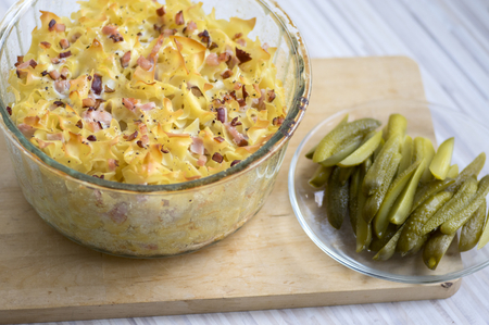 Baked meal from pasta, smoked meat and eggs called sunkofleky served with pickles, wooden mat