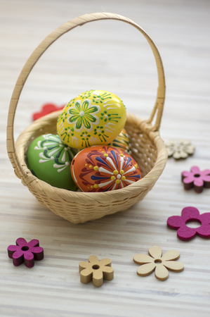 Wax painted Easter eggs in light brown wicker basket, wax ornaments, flower decorations spread on the table,