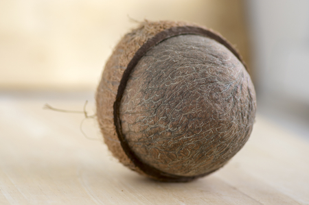 Full coconut with nutshells on wooden bambo table, tasty brown nut fruit