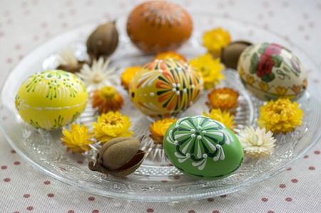 Group of wax painted Easter eggs spread on white transparent plate, flower ornaments, traditional decoration on brown spoted tablecloth