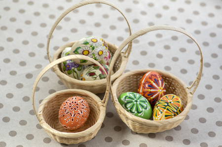 Group of wax painted Easter eggs in light brown wicker baskets, wax flower ornaments, traditional decoration on brown spoted table Stock Photo