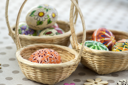 Group of wax painted Easter eggs in light brown wicker baskets, wax flower ornaments, traditional decoration on brown spoted table, wooden flowers