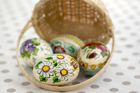 Group of wax painted Easter eggs spilled from light brown wicker baskets,flower ornaments, traditional decoration on brown spoted table