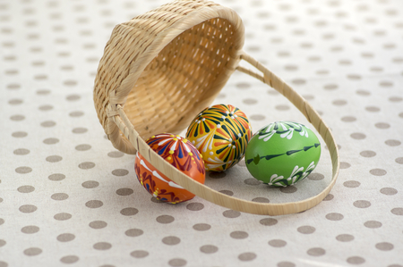 Group of wax painted Easter eggs spilled from light brown wicker baskets, wax flower ornaments, traditional decoration on brown spoted table