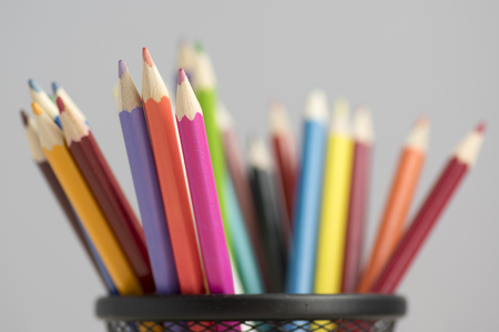 Close up of wooden colorful pencils, group of scattered crayons, isolate od white background in black metallic wire tin