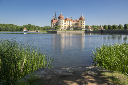 Castle Moritzburg in Saxony near Dresden in Germany surrounded by pond, reflection blue lake, blue sky and greenery