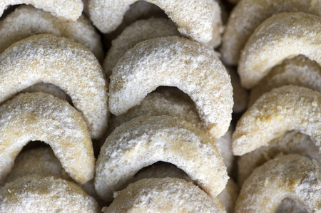 Traditional czech sweet Christmas cookies, vanilla rolls with white icing, cookies in the rows