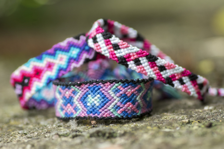 Three handmade homemade colorful natural woven bracelets of friendship isolated on grey stone background, detail view