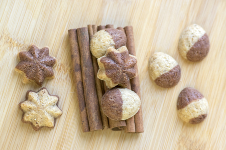 Cinnamon sandbakelse christmas cookies, two color, cocoa dark brown and vanilla light golden brown, cinnamon raw bark spice, stars and nuts shapes on wooden background 免版税图像