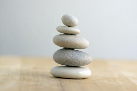 Stone cairn on striped grey white background, five stones tower, simple poise stones, simplicity harmony and balance, rock zen sculptures Stockfoto