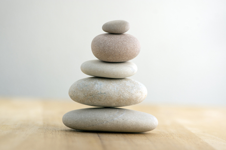 Stone cairn on striped grey white background, five stones tower, simple poise stones, simplicity harmony and balance, rock zen sculptures 写真素材