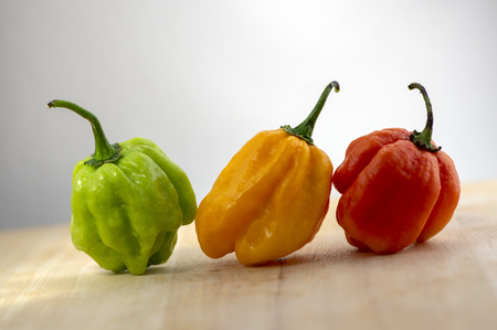 Three hot peppers habanero, various color on wooden table, mexican cuisine very hot ingredients, ripened and unripened fruits, green, orange and yellow