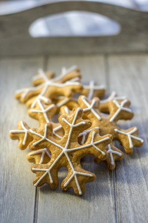 Painted traditional Christmas gingerbreads arranged on wooden tray in daylight, group of snowflakes, white sugar icing, simplicity arrangement