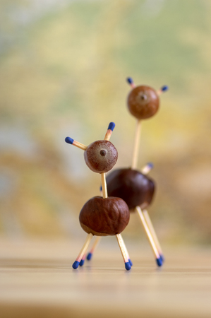 Group of funny chestnut animals on wooden table, fall background, traditional autumn handcraft, European roe deer with family made from autumn fruits and safety matches