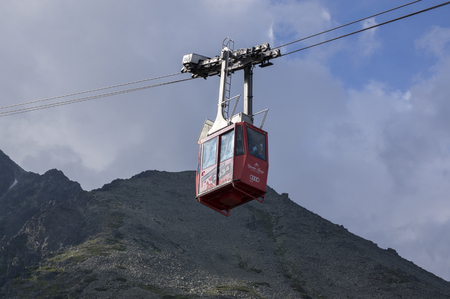 Lomnicky stit, High Tatra mountains / SLOVAKIA - July 6, 2017: Amazing aerial lift full of tourists from station Skalnate pleso to mount Lomnicky stit, red cabin cable car