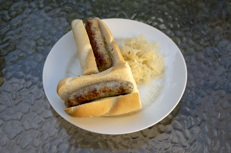 German sausages called bratwursts roasted in baguette with mustard, onion and pickled sauerkraut on white plate in Bosna style, fast food Zdjęcie Seryjne