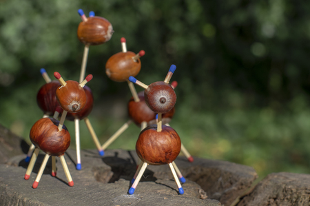 Group of funny chestnut animals on tree stump, green background, traditional autumn handcraft, European roe deer with family made from autumn fruits and safety matches