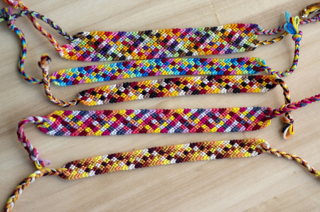 Five handmade homemade colorful natural woven bracelets of friendship on wooden board, group of fashion accessories, various colors, checkered pattern Imagens