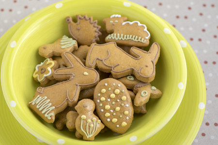 Czech painted easter gingerbread in light green bowl on dotted tablecloth, comical bunnies and various shapes
