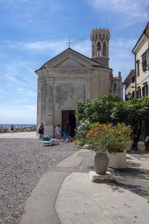 Our Lady of Health Church, Piran / SLOVENIA - June 24, 2018: Peninsula Piran coastline with church and tourists enjoying sunny day