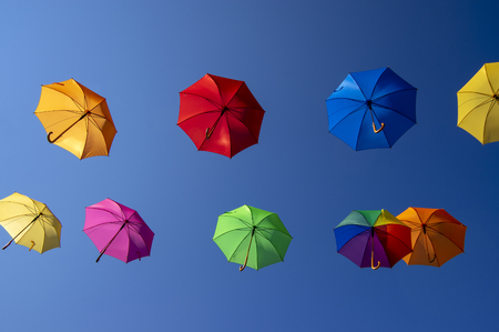 Group of flying umbrellas isolated on blue background, ready for the rain, wallpaper background, bright various colors, beautiful still life