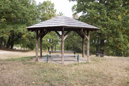 Simplicity wooden shelter with seats in nature, small gazebo for tired tourists, surrounded by trees