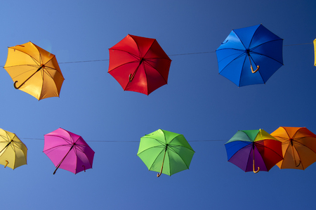 Group of flying umbrellas isolated on blue background, ready for the rain, wallpaper background, bright various colors, beautiful scene