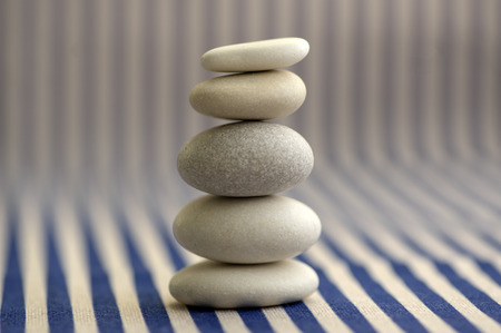 Harmony and balance, pebble rock cairn, simple poise stones on white and blue striped background, rock zen sculpture, five white pebbles, single tower, simplicity