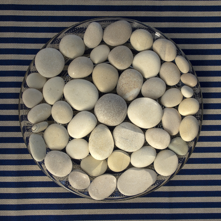 Circle composed of white and gray stones, pebbles mandala background on blue white striped background in daylight, life concept, sunlight Banco de Imagens