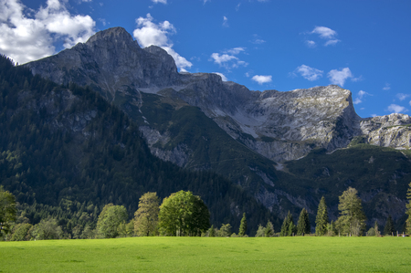 Austrian Verfenveg village Alps mountains autumnal scenery with fog, green meadows and rocks, amazing view