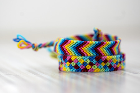 Two handmade homemade colorful natural woven bracelets of friendship isolated on light wooden background, rainbow bright colors, beautiful accessories